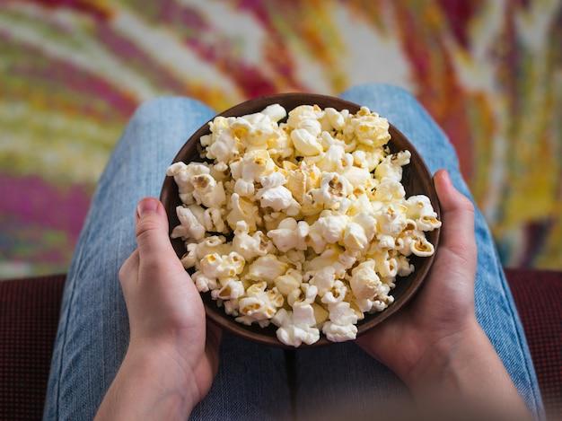 Baby in einem stuhl auf einer bunten oberfläche mit einer schüssel popcorn.
