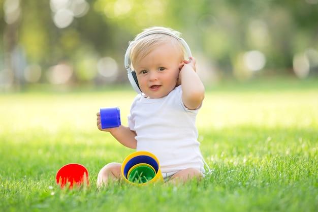 Baby in einem weißen body, der auf dem spielen des grünen grases sitzt