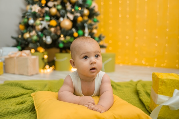 Baby in einem weißen bodysuit, der auf einem gelben kissen mit weihnachtsbaum liegt