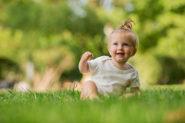 Baby in einem weißen sandkasten auf dem spielen des grünen grases