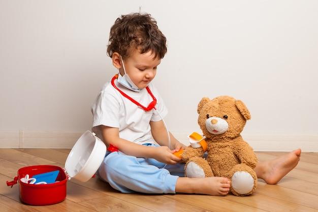 Baby in einer medizinischen maske spielt mit einem teddybär. baby in einer maske setzt auf eine maske ein spielzeug.