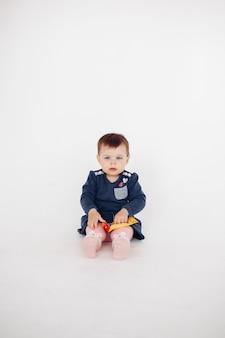 Baby in kleid und strumpfhose mit spielzeug auf dem boden