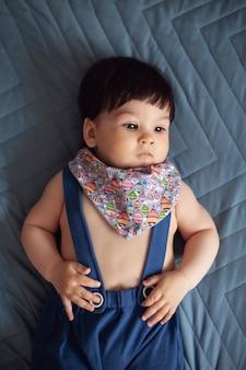 Baby in lätzchen und blauen hosenträgerhosen lächeln auf der blauen oberfläche