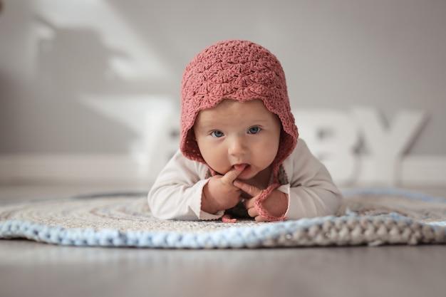 Baby in mütze in echtem kinderzimmer, sicherheit und pflege