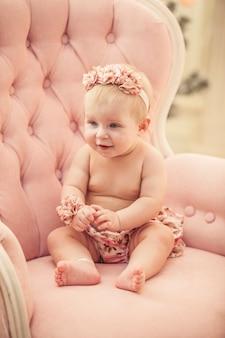 Baby in rosa kleidern und glücklichem interieur im retro-stil