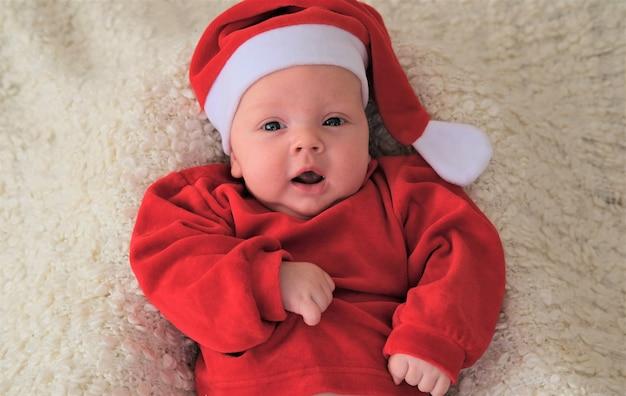 Baby in rotem kostüm und hut. schönes kleines baby feiert weihnachten.
