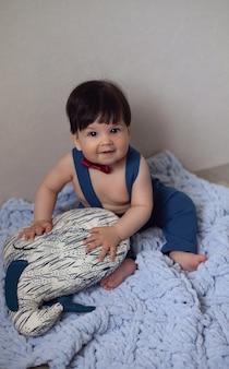 Baby in roter krawatte und blauer hosenträgerhose
