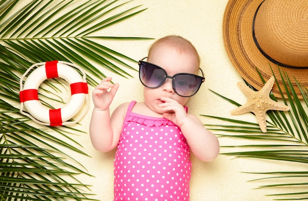 Baby in sonnenbrille mit strandaccessoires. urlaub auf see mit baby, sommerkonzept