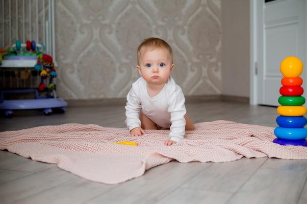 Baby in weißen kleidern sitzt auf dem boden auf einer gestrickten decke und spielt mit lernspielzeug, platz für text