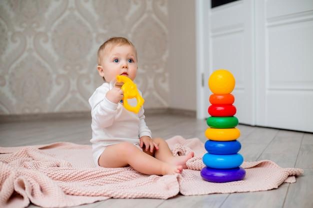Baby in weißen kleidern sitzt auf dem boden auf einer gestrickten decke und spielt mit lernspielzeug