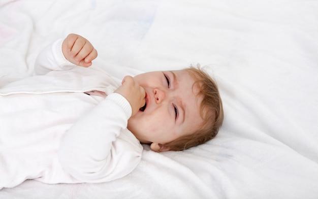 Baby ist verärgert und weint mit der hand im mund