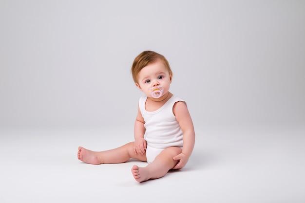Baby junge in einem weißen body mit einem schnuller im mund sitzt auf einem weißen hintergrund