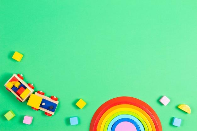 Baby kinder spielzeug hintergrund. holzzug, stapelspielzeugregenbogen, flugzeug und bunte blöcke auf weißem hintergrund