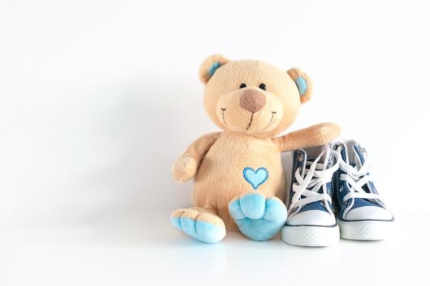Baby kleine schuhe turnschuhe und teddybär auf holz weißen tisch hintergrund baby mode stil