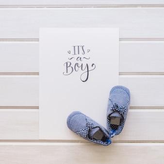 Baby-konzept mit papier und paar schuhe auf holzoberfläche