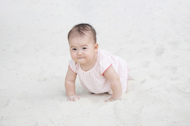 Baby kriecht auf dem sand