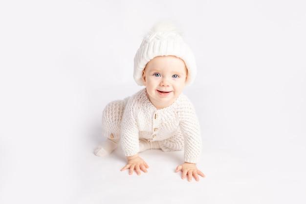 Baby kriecht in einem warmen anzug und hut auf einem weißen isolierten hintergrund, raum für text