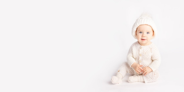 Baby kriecht in einem warmen anzug und hut auf einem weißen isolierten hintergrund