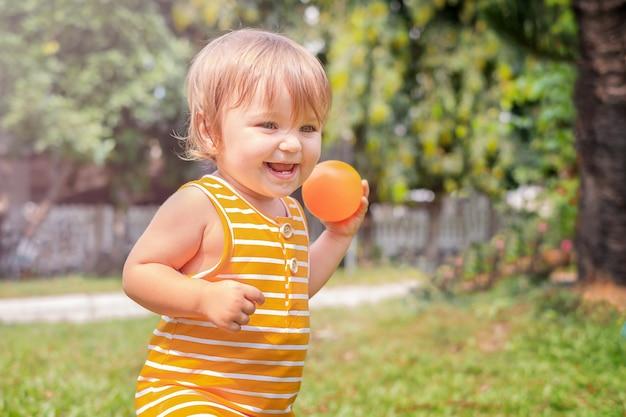 Baby läuft auf dem gras im hinterhof, der mit einem ball spielt