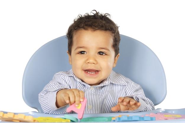 Baby lernen die buchstaben, die über weißem hintergrund spielen
