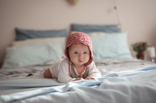 Baby liegt auf bett im wirklichen hellen kinderzimmer