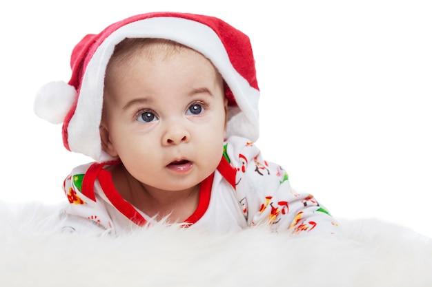 Baby liegt auf dem bauch in einer weihnachtsmannmütze mit einem überraschten
