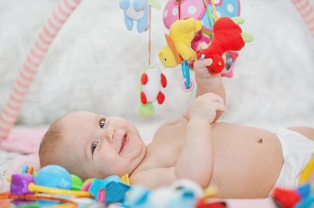 Baby liegt auf entwicklungsteppich. in mobile spielen. lernspielzeug. süßes kind, das kriecht und mit spielzeug auf teppich spielt
