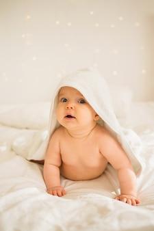 Baby liegt in einem weißen handtuch mit einer kapuze auf weißer decke auf dem bett