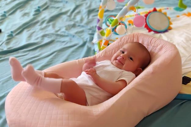 Baby liegt in einer speziellen orthopädischen matratze auf einem bett und lächelt
