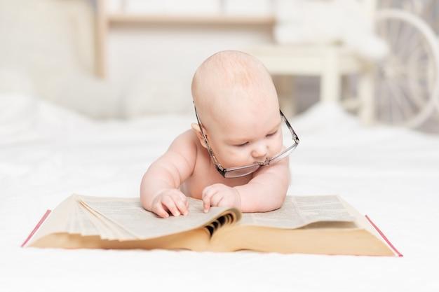 Baby liest ein buch mit brille oder betrachtet es im kinderzimmer, lern- und entwicklungskonzept