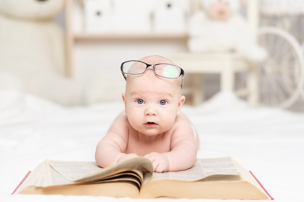 Baby liest ein buch oder schaut es im kinderzimmer an, lern- und entwicklungskonzept