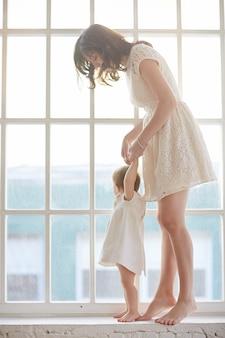Baby macht erste schritte mit der hilfe der mutter zu hause baby lehnt sich mit der mutter spazieren