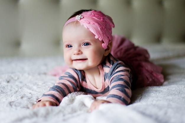 Baby mädchen auf dem bauch liegen und lächelt auf dem bett in kleidung und einem rosa stirnband