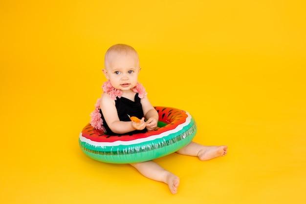 Baby mädchen im schwarzen und rosa badeanzug, der aufblasbaren pool der wassermellone hält auf gelbem hintergrund mit kopienraum.