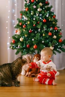 Baby mädchen in einem rot-weißen strickkostüm streichelt eine katze vor einem weihnachtsbaum. hochwertiges foto