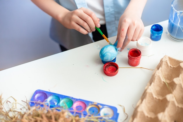 Baby malt ostereier mit pinsel und aquarell