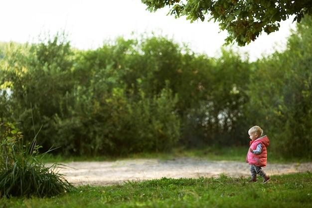 Baby mit blondem haar, das rosa weste trägt, die im grünen park geht, der die große und interessante welt erkundet