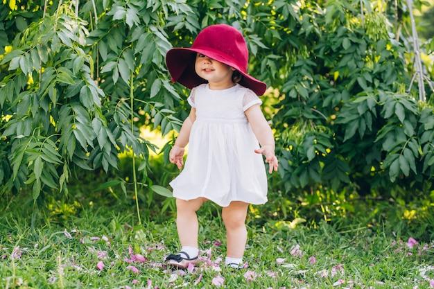 Baby mit blonden haaren in einem weißen kleid und im roten hut der mutter im sonnigen sommertag des parks.