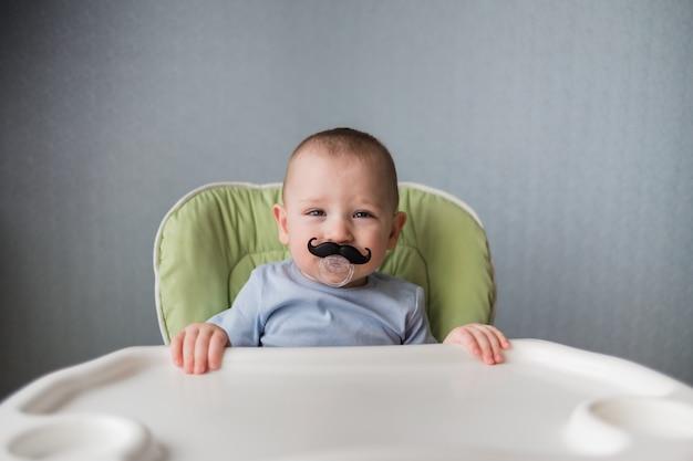 Baby mit einem schnuller in form eines schnurrbartes sitzt auf einem hochstuhl