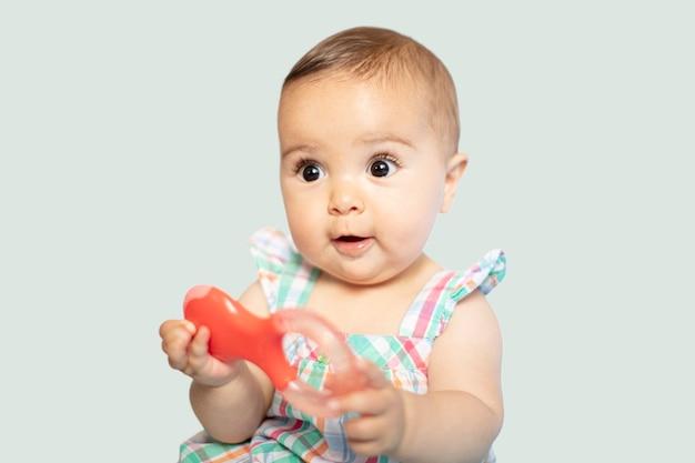 Baby mit einem spielzeug in ihrer hand auf weißem hintergrund mit kopienraum