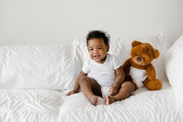 Baby mit einem teddybär auf dem bett