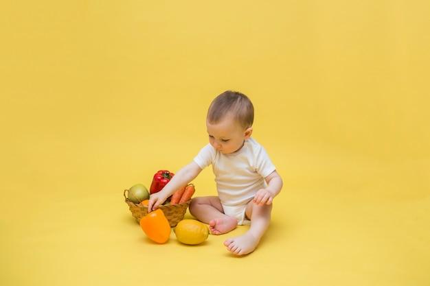Baby mit einem weidenkorb mit gemüse und obst auf einem gelben raum. der junge sitzt in einem weißen body und spielt mit zitrone und paprika.