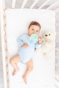 Baby mit einer flasche milch in den händen im krippenessen, babynahrungskonzept