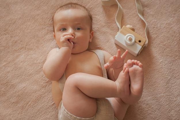 Baby mit einer holzkamera liegt auf einem beigen hintergrund, das baby lutscht am daumen