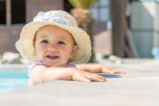 Baby mit hut beim swimmingpoollächeln