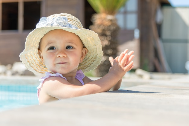 Baby mit hut im swimmingpool applaudierend