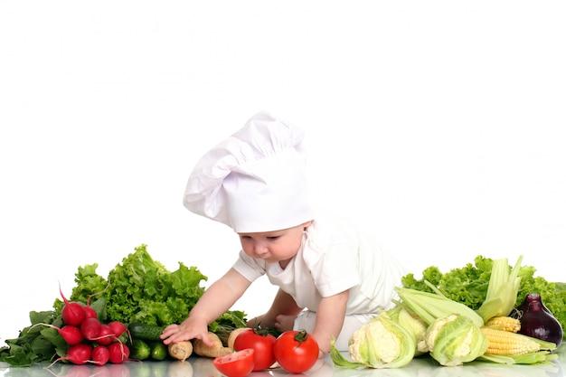 Baby mit hutkoch, umgeben von gemüse