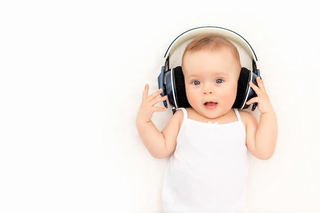Baby mit kopfhörern, die musik auf einem weißen bett zu hause hören