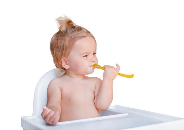 Baby mit löffel im babystuhl lokalisiert auf weißem hintergrund