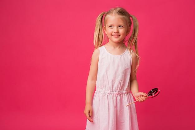 Baby mit lutscher auf rosa hintergrund